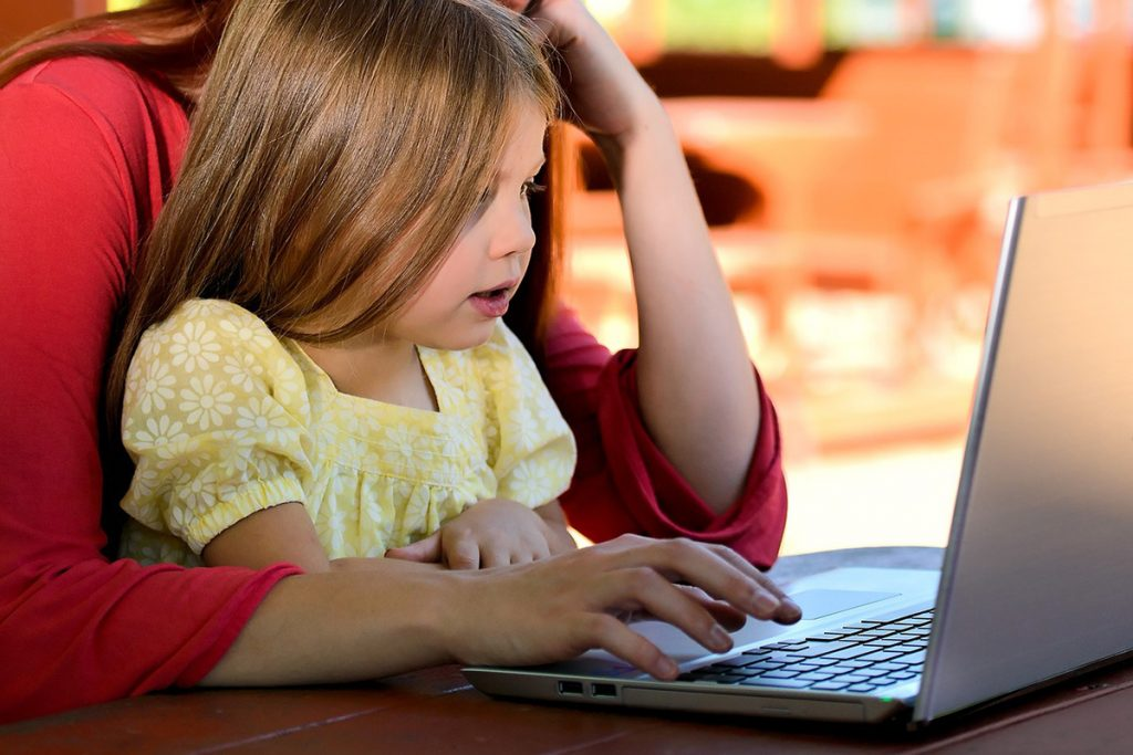 Young girl sitting by computer with her mother