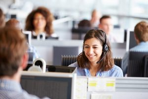 Young woman working in call center, staying in touch with end-customers during an outage.